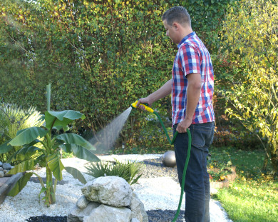 Mann der einen Garten gießt